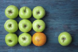 Green apples and one orange on blue wooden background